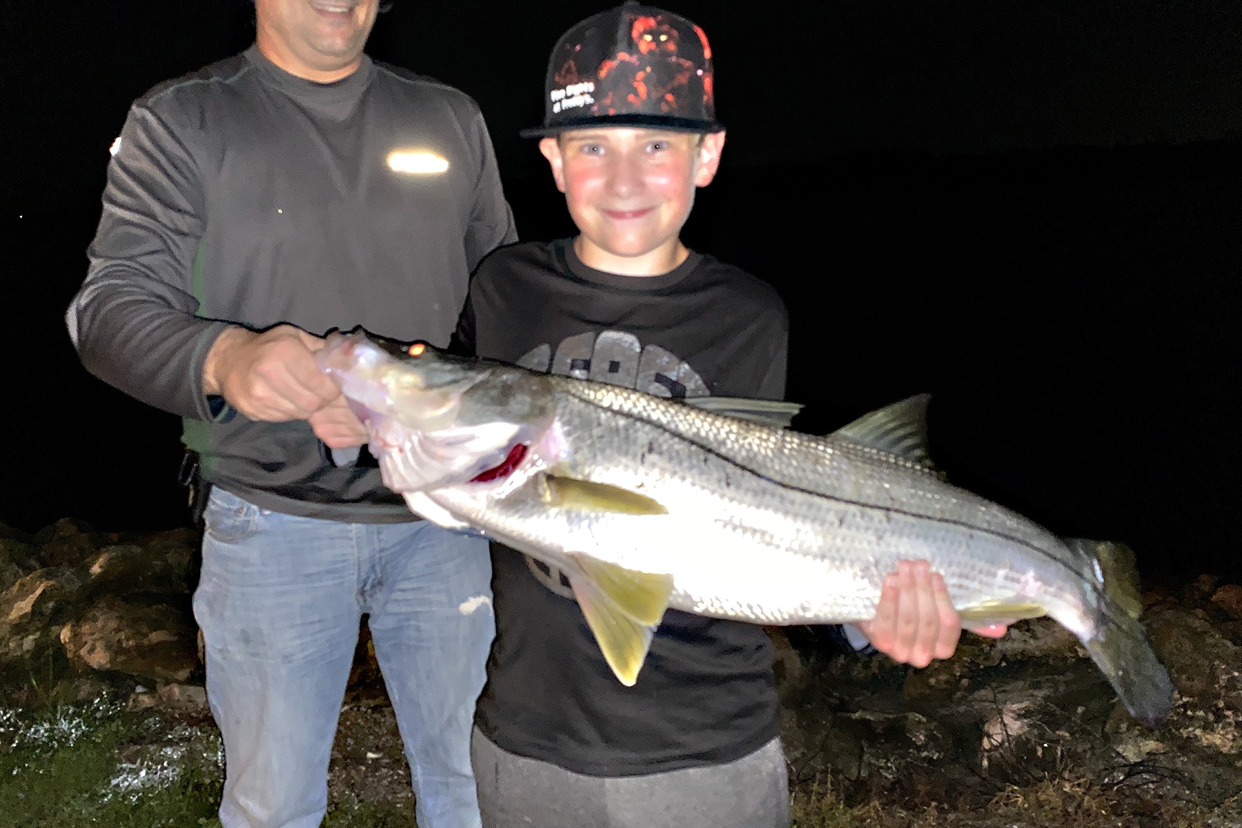 Young boy holding fish with man in background at night