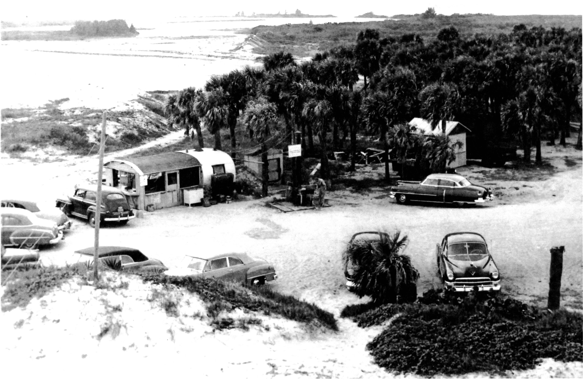1950s style cars parked in a lot at the inlet showing a ramschackle fish camp in background