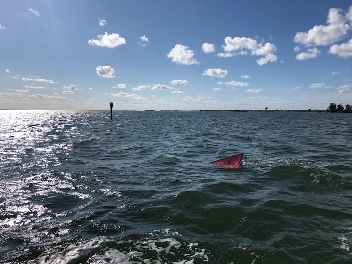 water with downed channel marker skimming surface