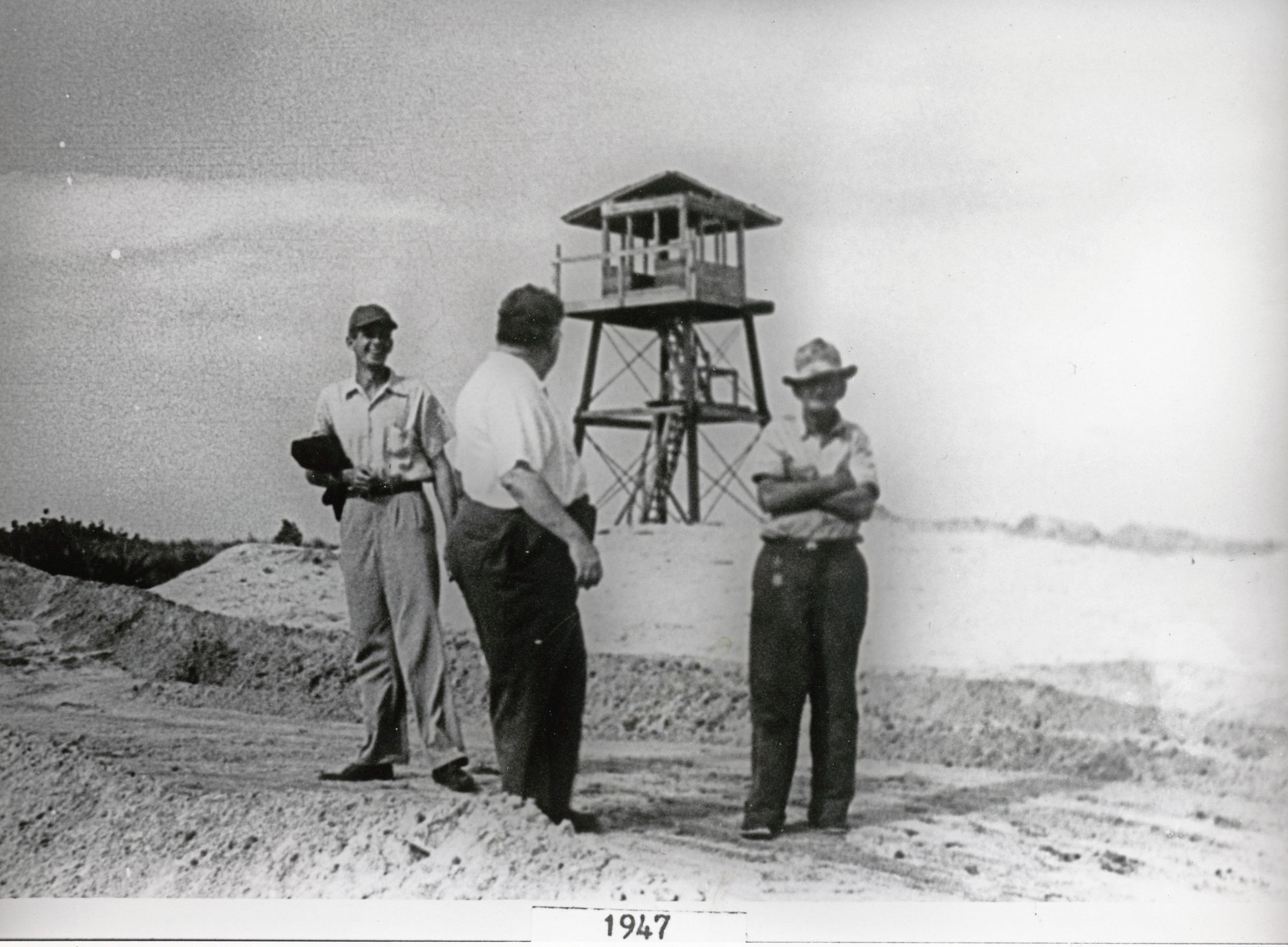 Three men standing on beach in front of wooden world war 2 spotting tower