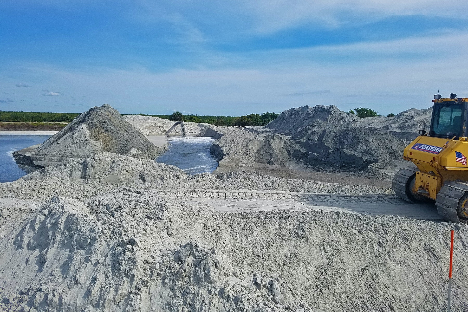 bulldozers working with mounds of sand and dredge pipe discharge in background