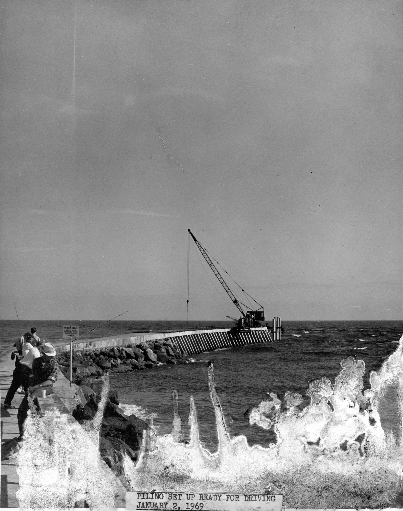 looking out over Atlantic Ocean from base on new north jetty with people in the foreground and construction crane on tip of jetty in background