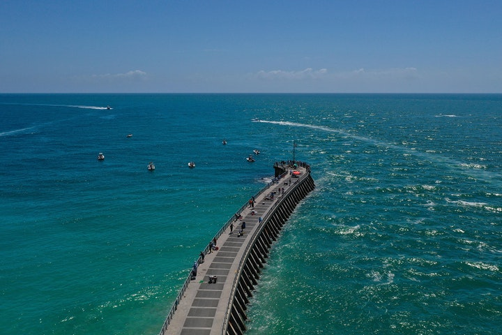 aerial view of jetty jutting out into sea with fisherman on pier and boats surrounding