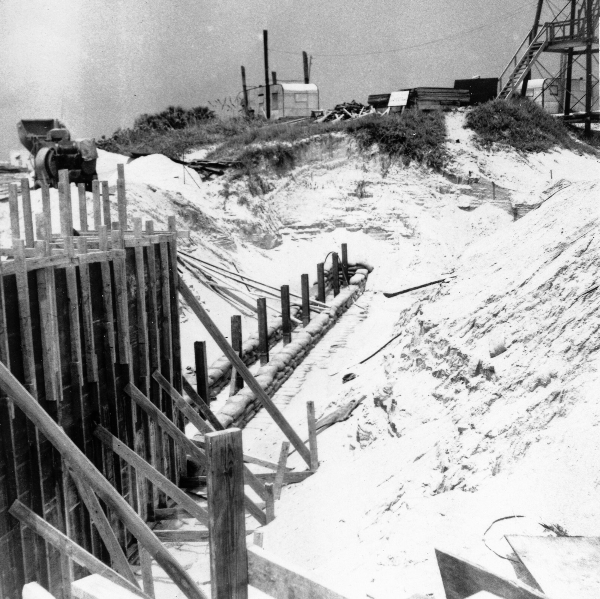 wooden support structure used to begin north jetty construction surrounded by a sand dune