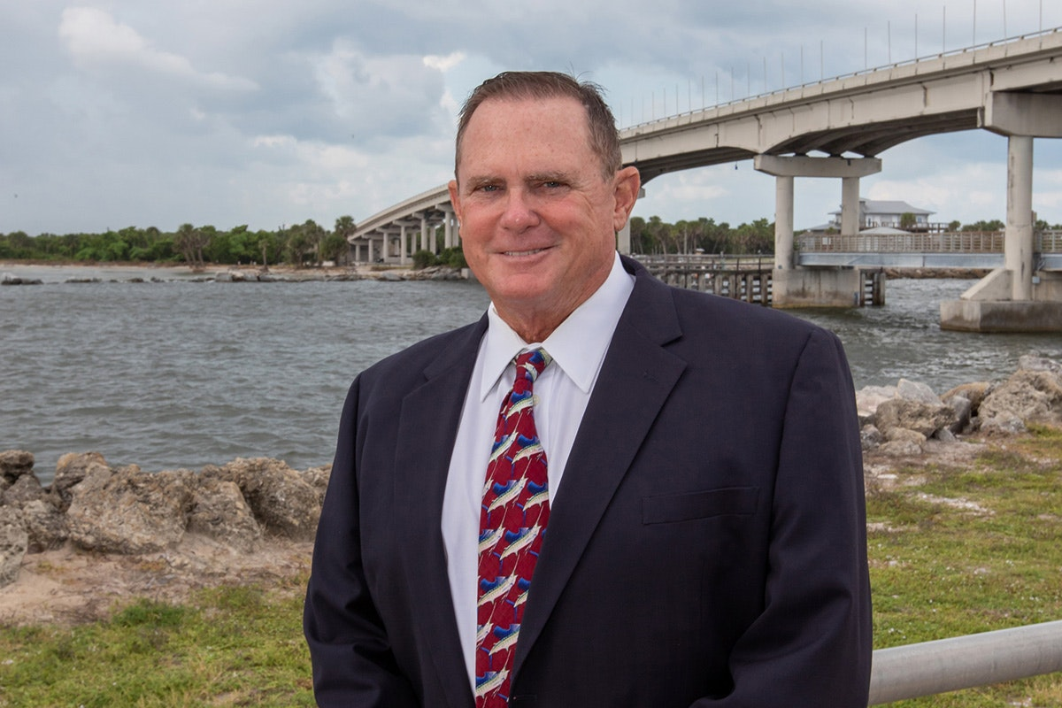 man standing in front of sebastian inlet and bridge