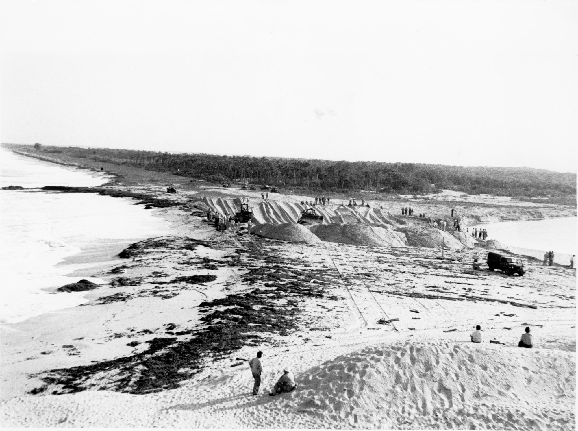 wide view of bulldozers working the final section of sand between the Indian River and the waters of the Atlantic Ocean