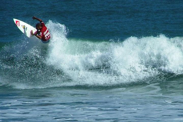 surfer Kelly Slater riding a wave