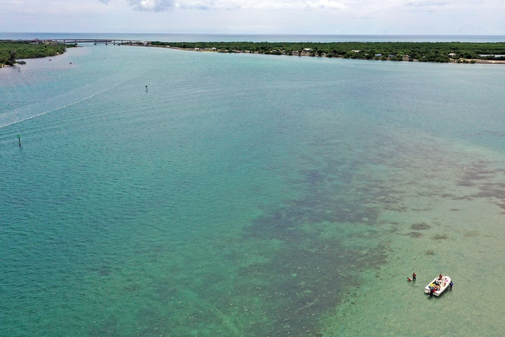 aerial view looking east of western flood shoal at Sebastian Inlet with lone boater in foreground