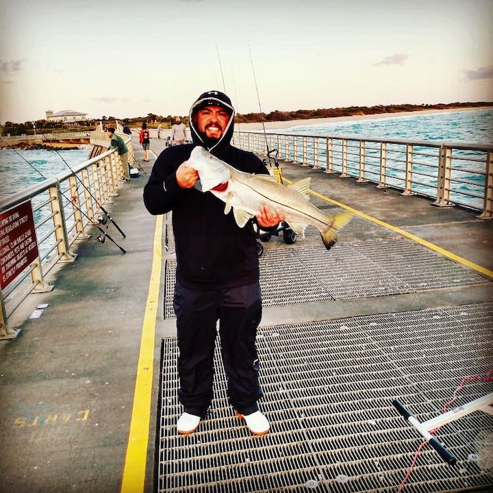 man holding snook on fishing pier
