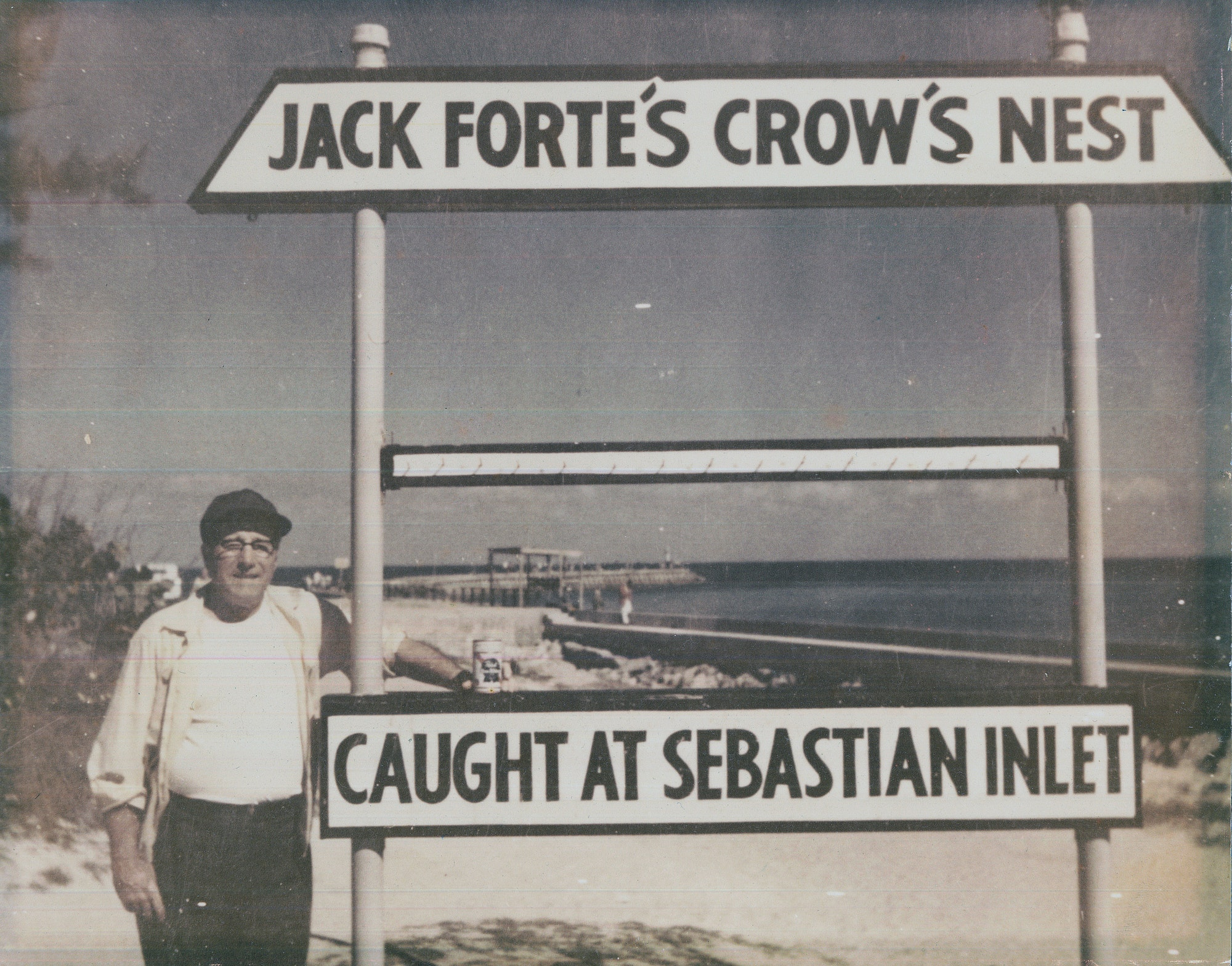 man standing in front of sign reading Jack Forte's Crow's Nest, Caught at Sebastian Inlet