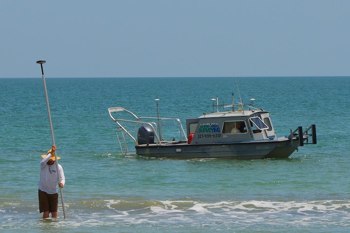 man standing in surf with equipment with boat in background