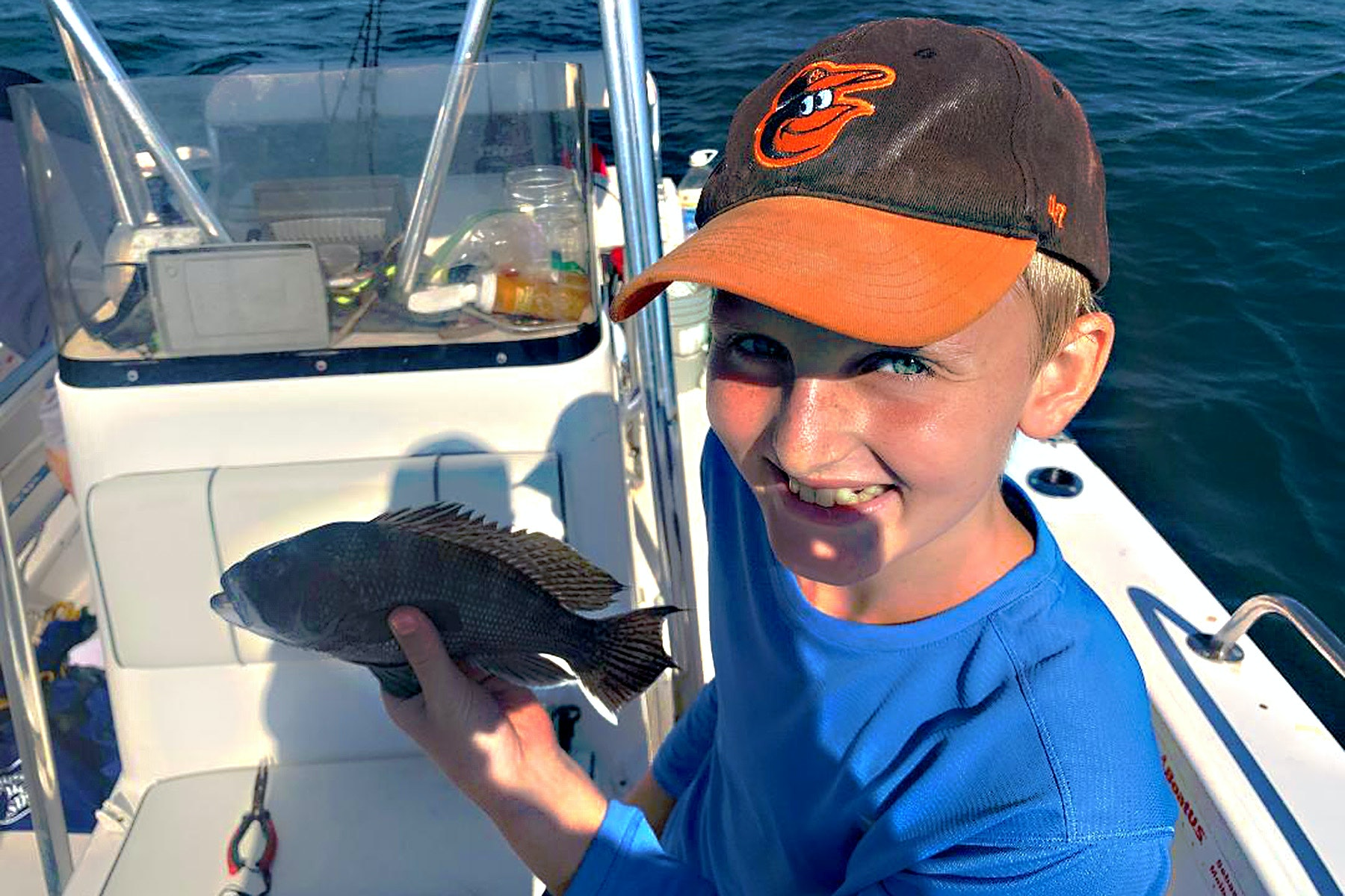 young boy in a ballcap holding a fish on a boat