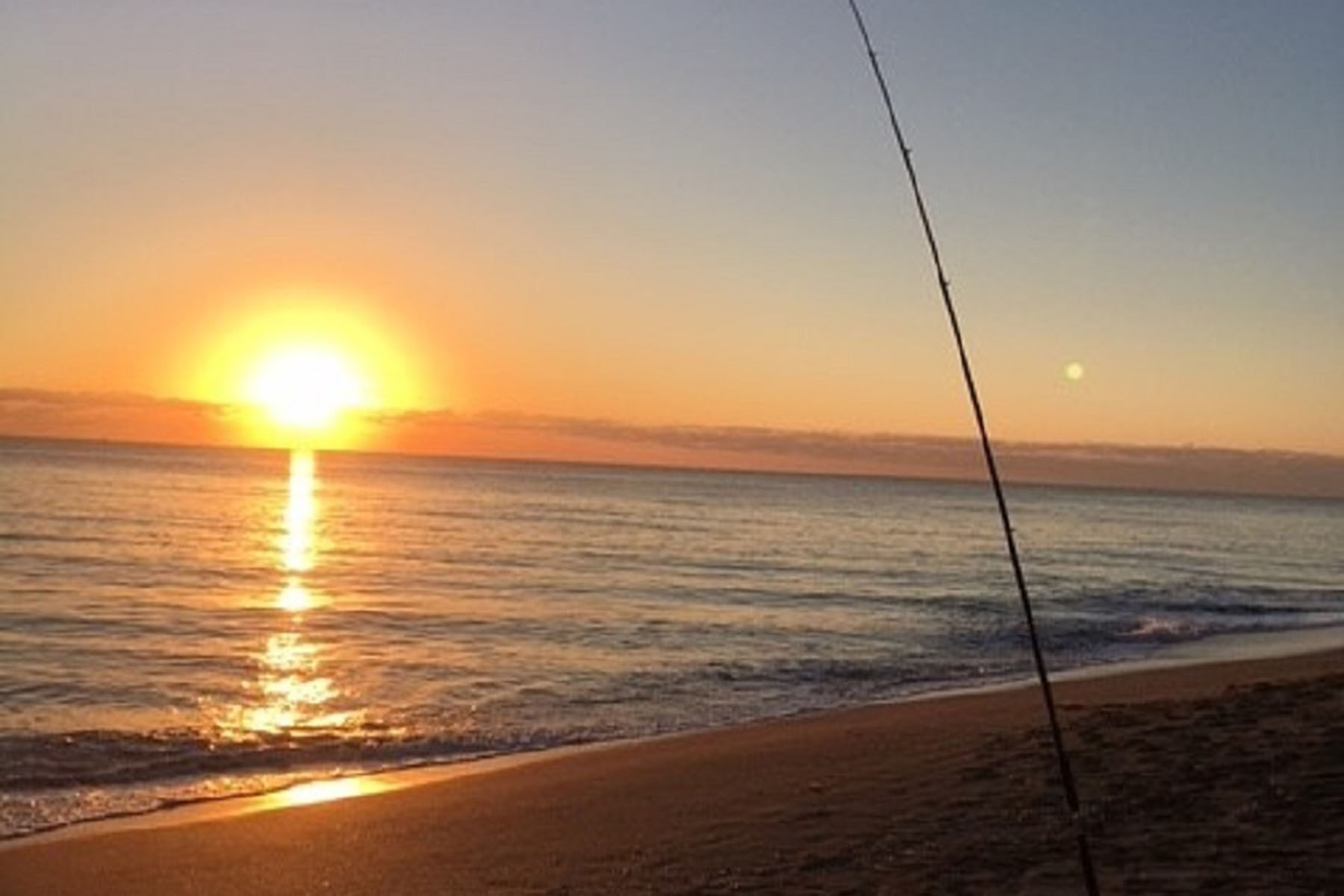 sunrise over the beach with fishing pole in sand