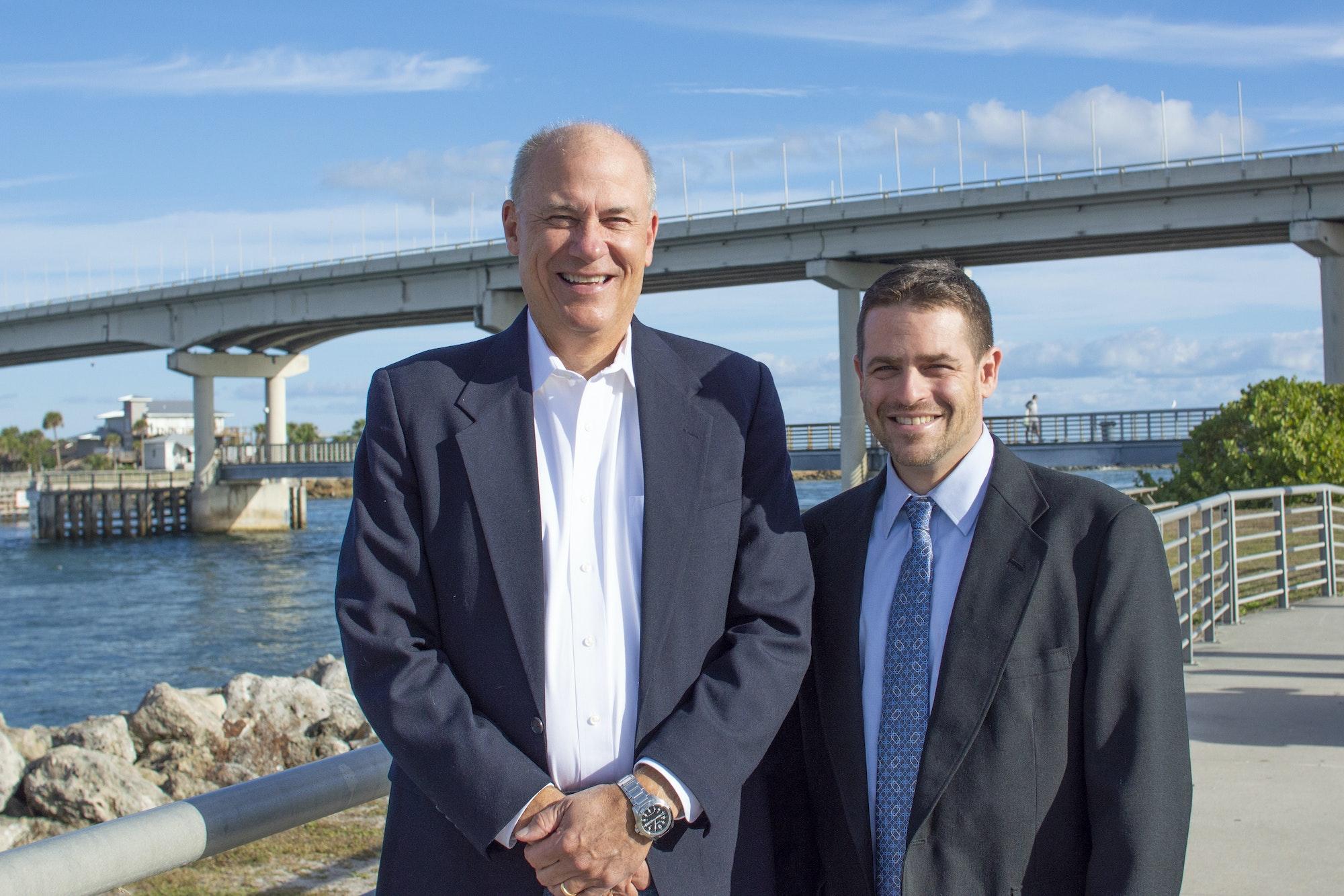 two men standing in front of bridge over inlet in background