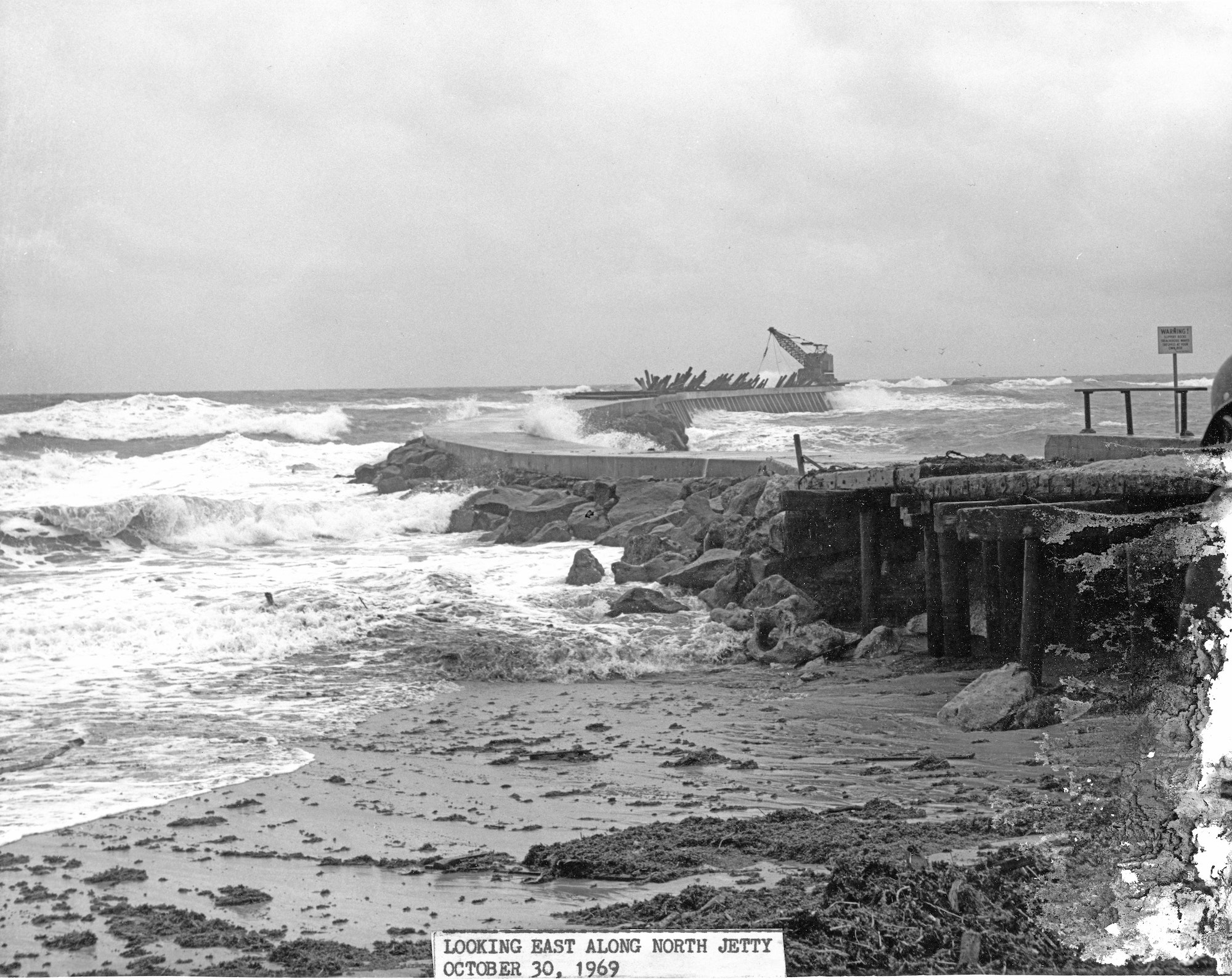 looking out from the base of north jetty with rough seas, damage to the jetty and crane stranded out on the tip