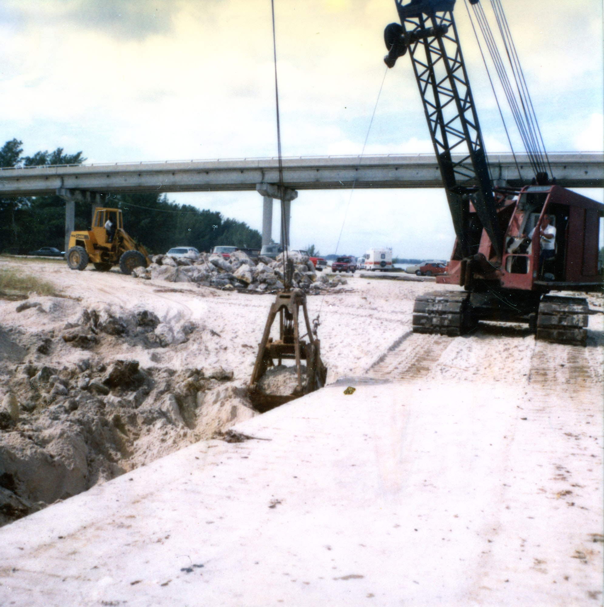 crane moving rocks and sand with bridge and bulldozer in background
