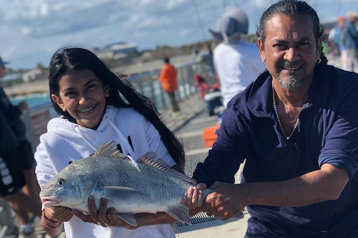 young girl and father holding black drum fish