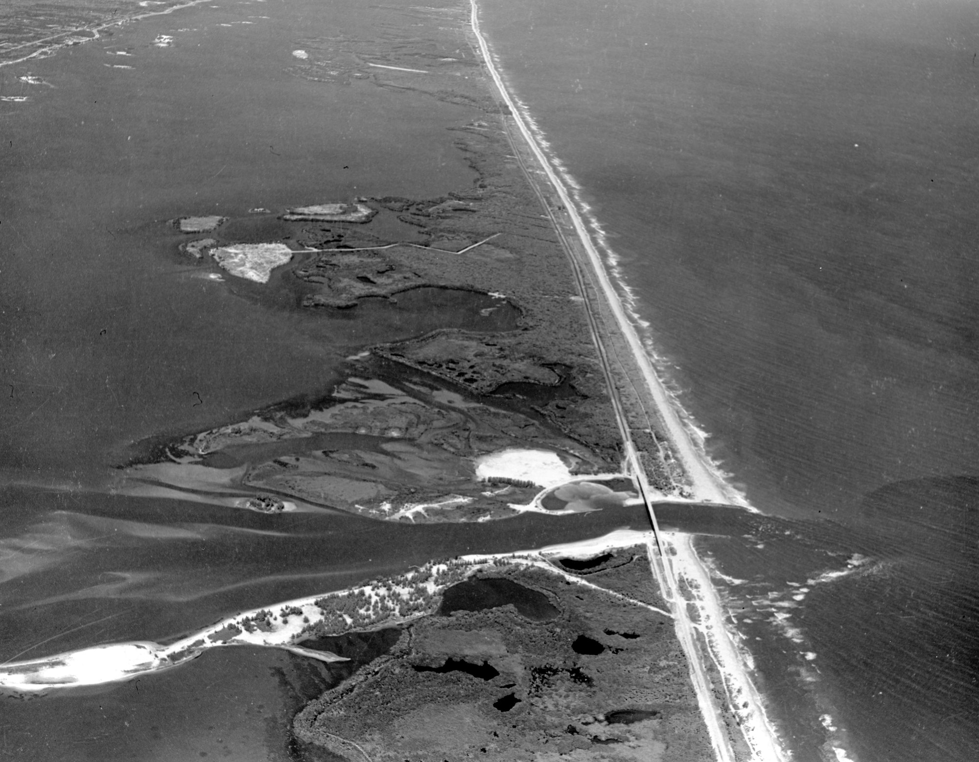 high altitude aerial view of the Sebastian Inlet from 1966 looking North over the inlet, lagoon and coastline