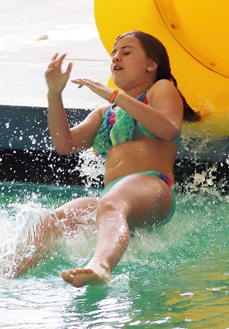 Girl going down pool slide