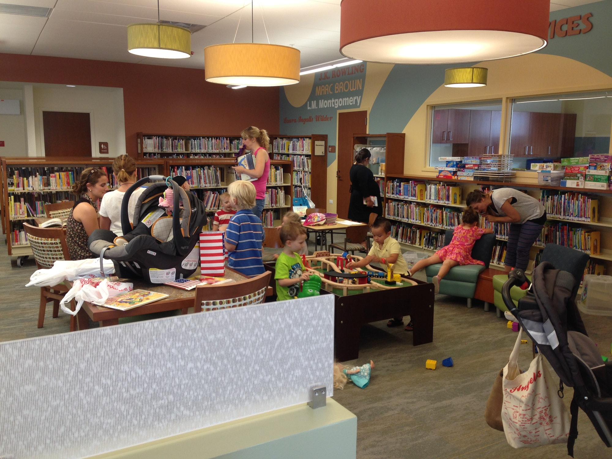 Children play with toys and parents browse books in the kids area