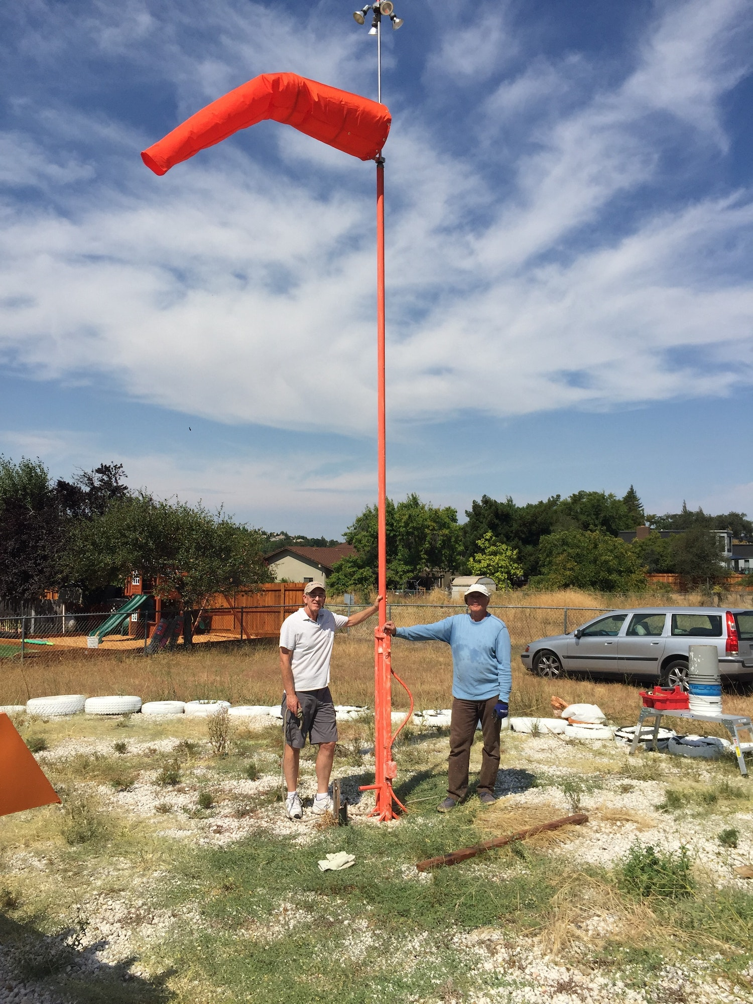 Two volunteers standing at base of flag pole where they installed a new wind sock