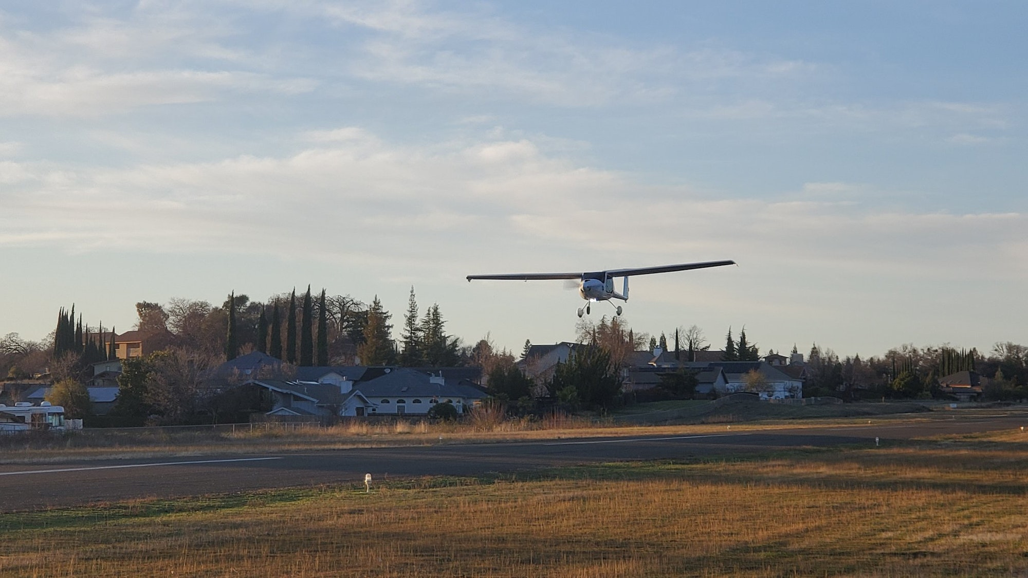 A small aircraft is landing on a late afternoon
