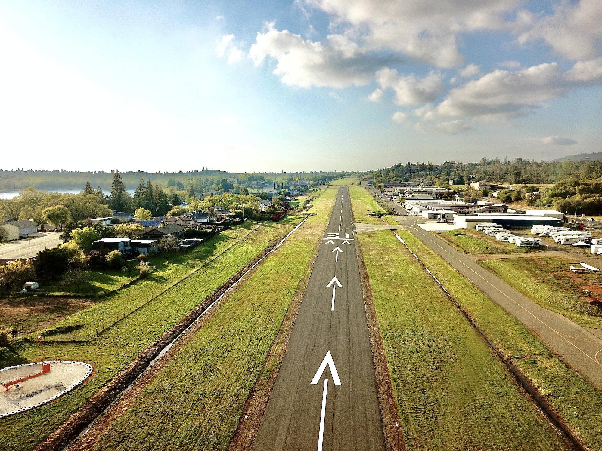 View of runway surrounded by lush grass on a sunny day