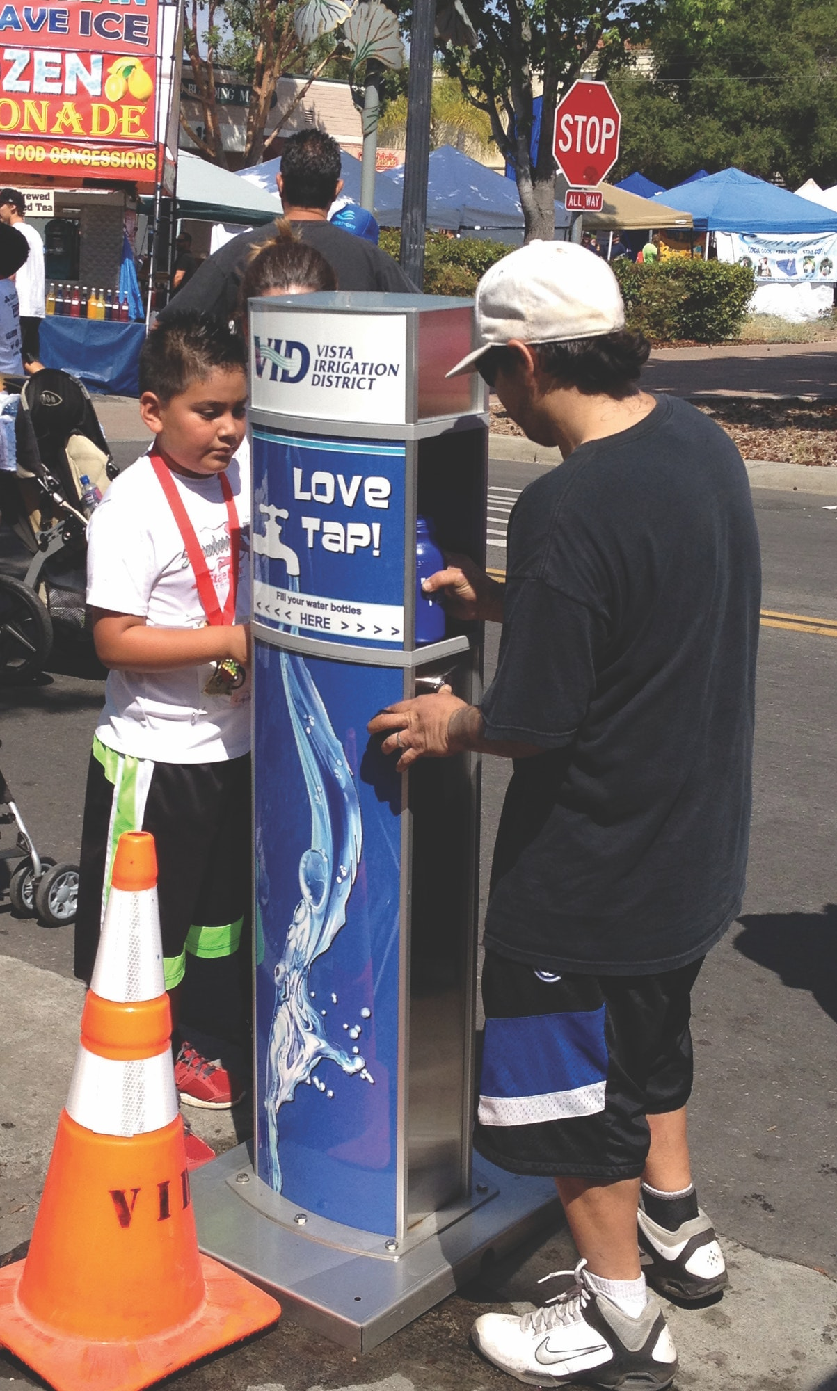 Customers filling reusable water bottles at hydration station.
