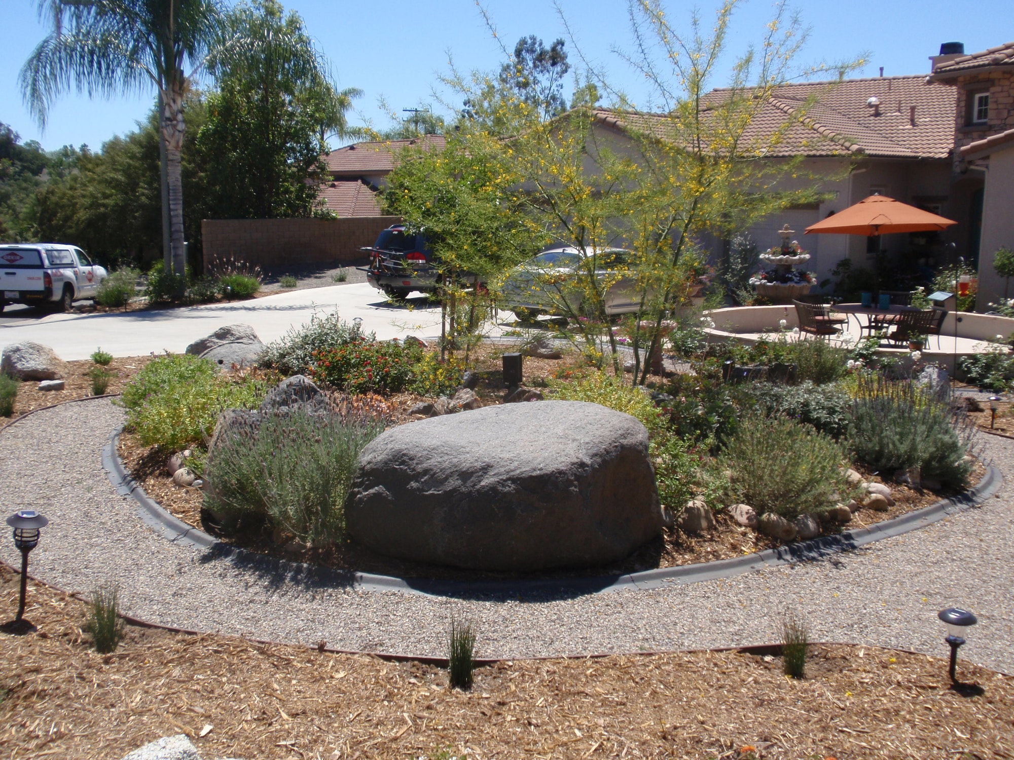 Photograph of WaterSmart landscaping at a residential home, that includes Palo Verde tree, landscaping boulders and gravel pathway.