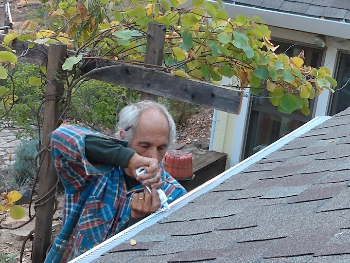Squeezing silicone caulking on gutter guards