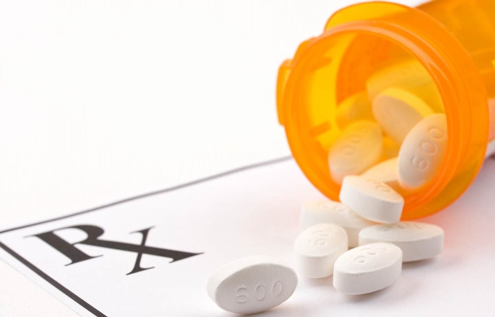 prescription paper and pills coming out of an orange container