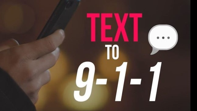 "Image of hand holding a cell phone and ""TEXT TO 9-1-1"" in red and white letters."