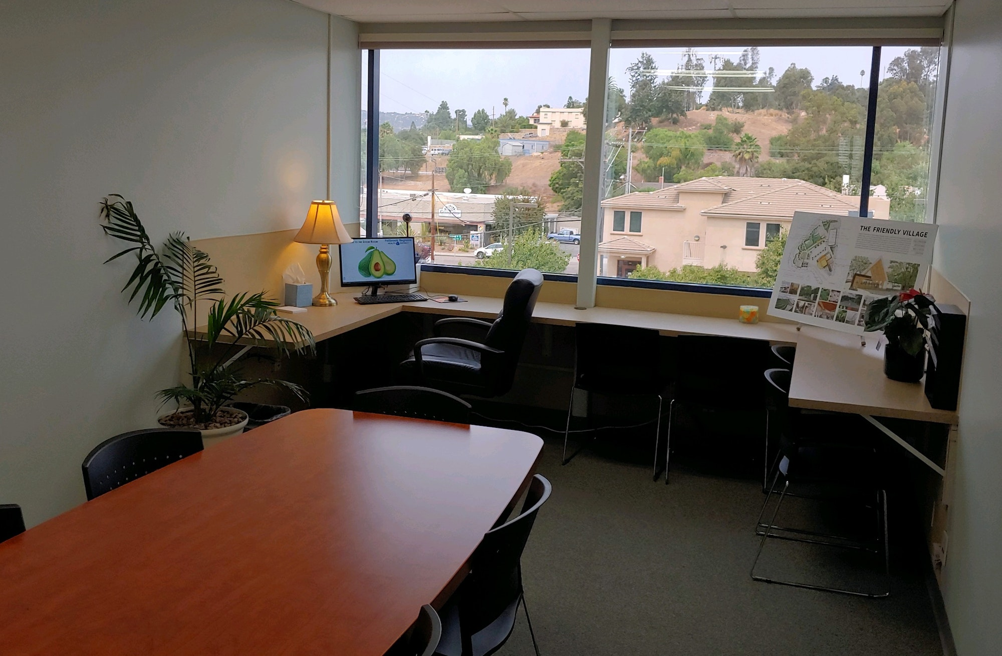 Photograph of room with a table, built-in desk, chairs and computer.