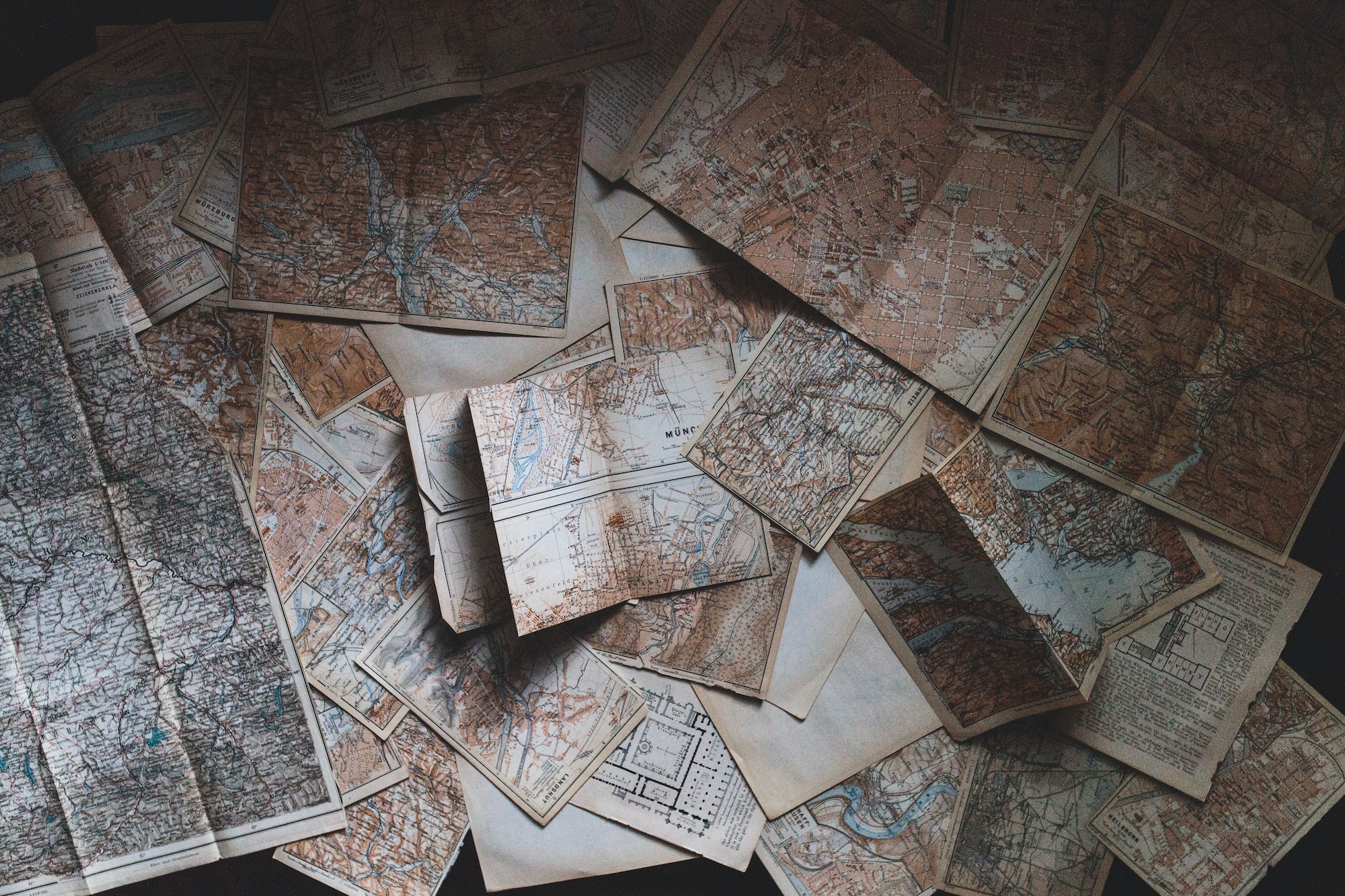 Maps haphazardly placed on a table.