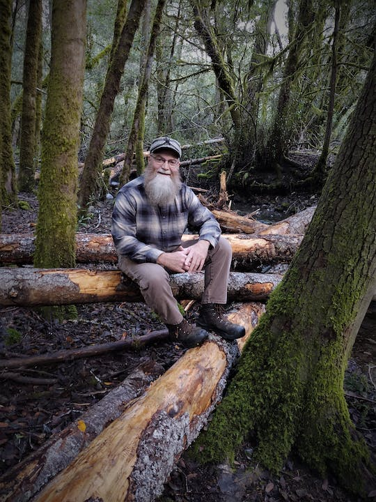 Kevin seated on a log structure in Page Creek