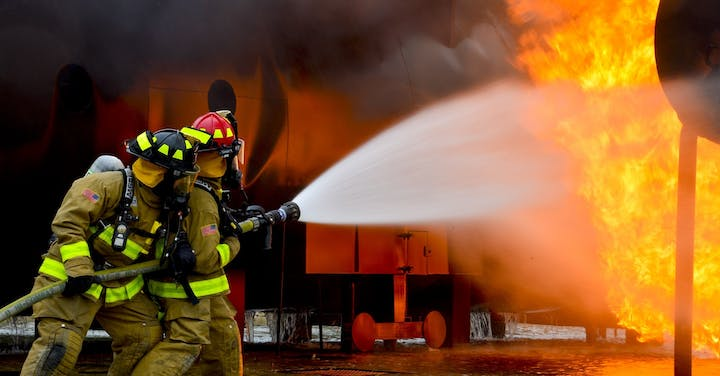 A pair of firefighters battling a blaze with a hose