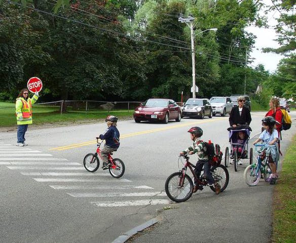 School children on bikes with crossing guard