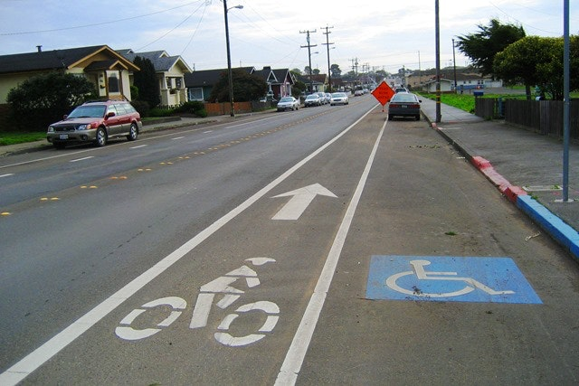 May contain: bike lanes, handicapped parking space, road, car, transportation, vehicle, automobile, street, building, urban, city, and town