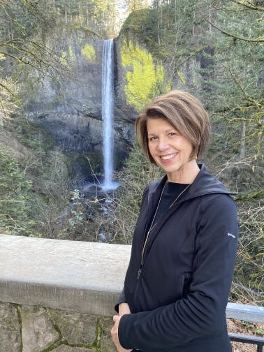 Board member Susan Stovall standing in front of a waterfall.