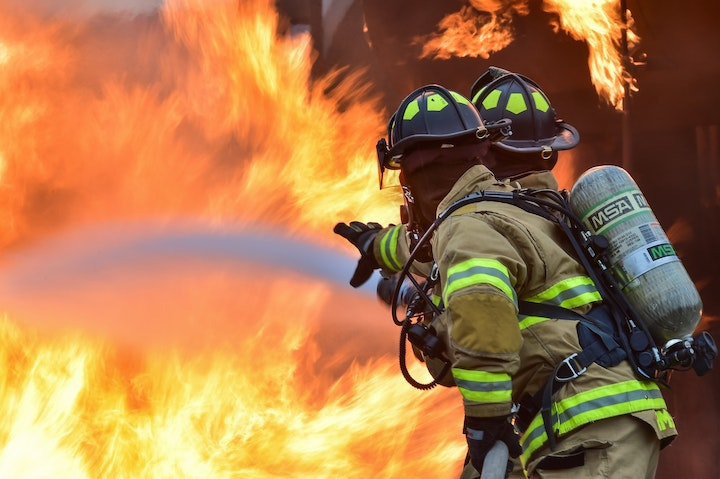 Two firefighters battling a blaze with a hose