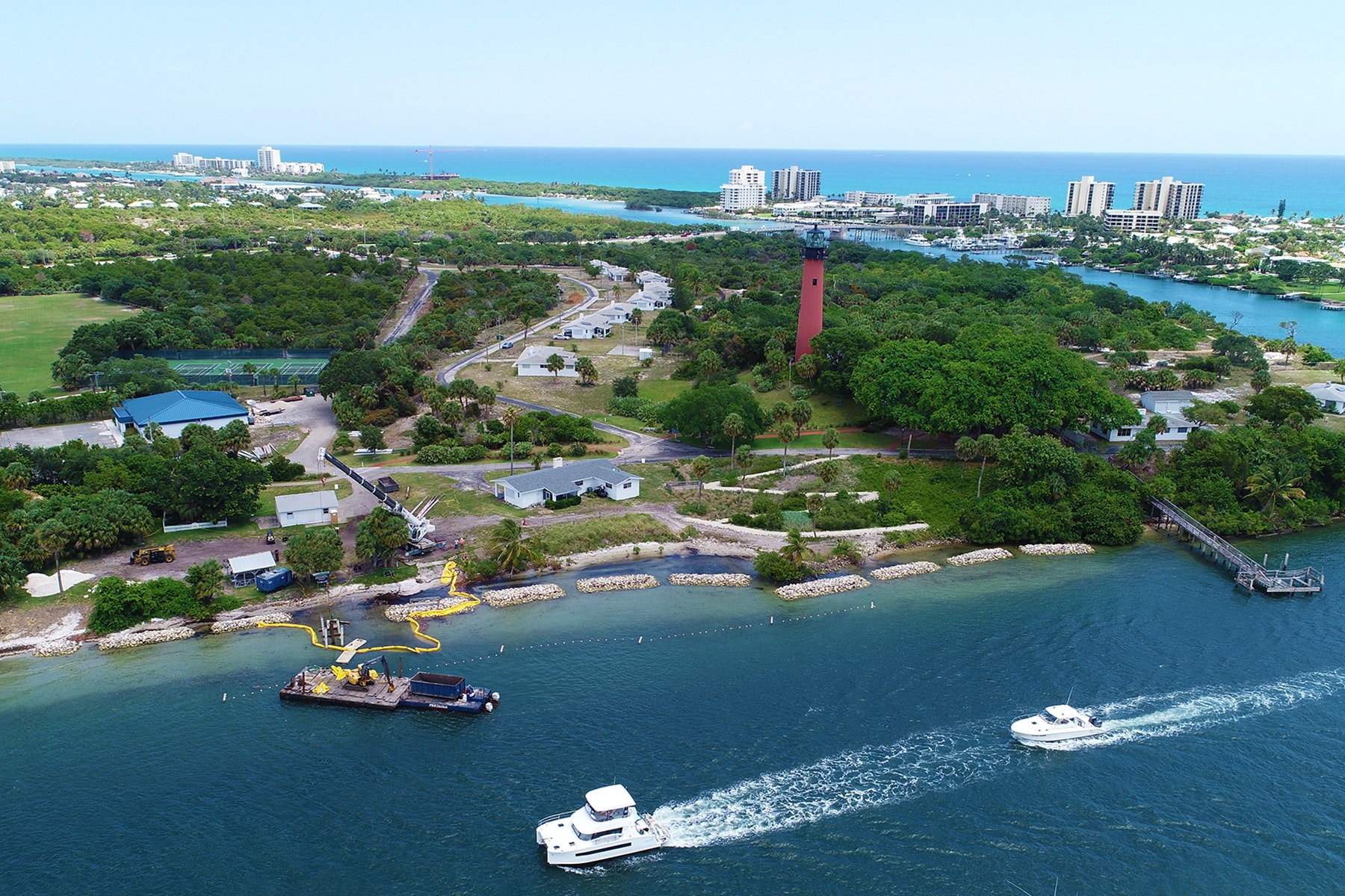 waterway with dredge and boats navigating by in front of Jupiter Lighthouse with nearshore breakwaters being constructed