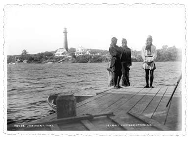 1891 black and white photo with three people standing on dock with water and the Jupiter lighthouse in the background