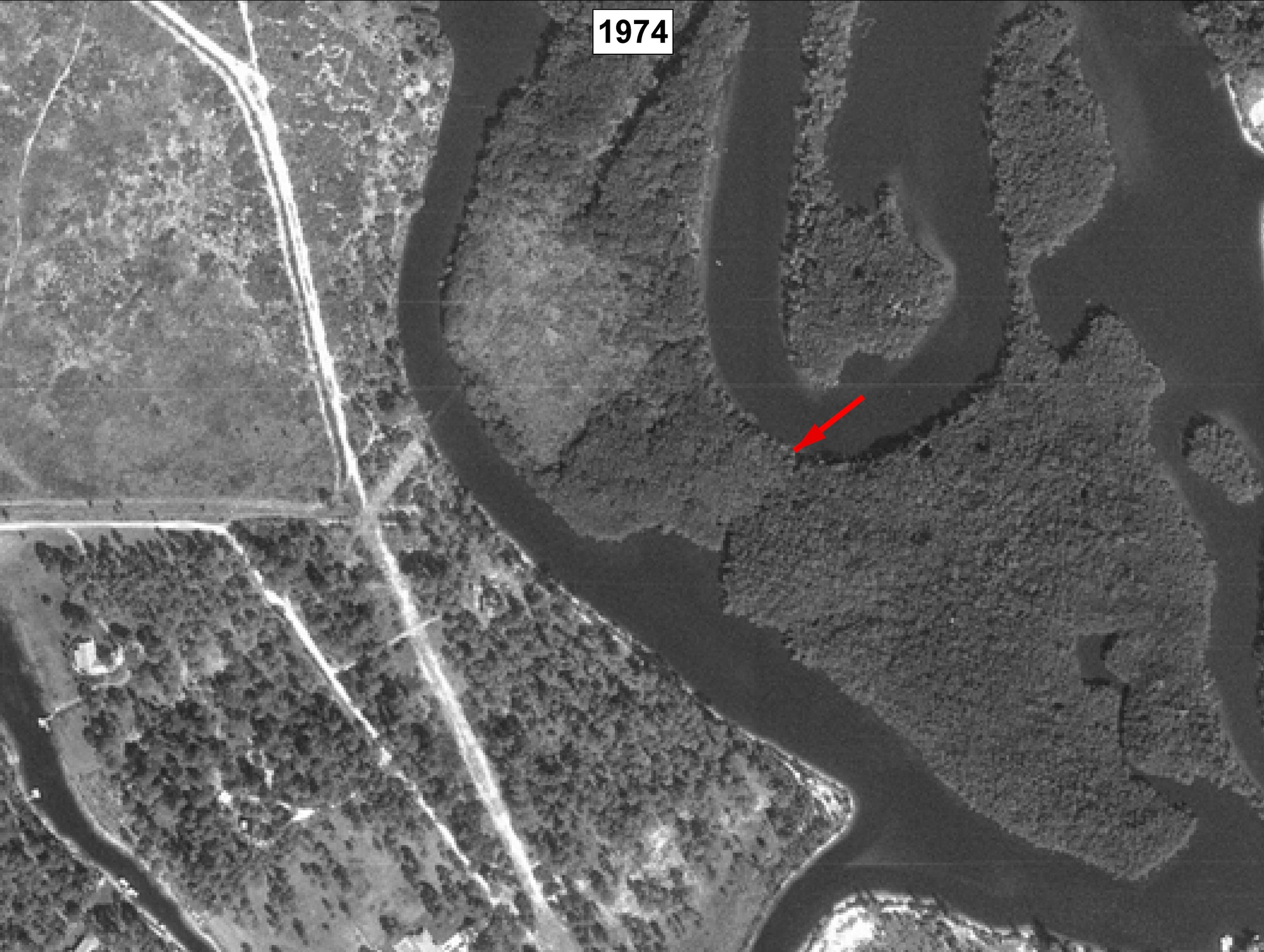 aerial view of meandering river with undeveloped land, red arrow and labeled 1974