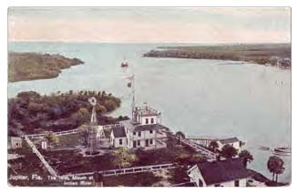 postcard image of photo from the Jupiter Lighthouse looking east across the waters of the inlet with the U.S. Weather Bureau building in the foreground