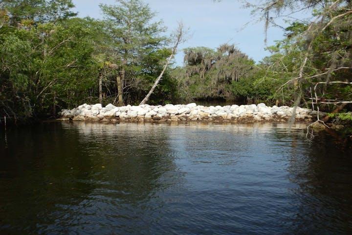 Limestone rock wall blocking waterway with native foliage on banks