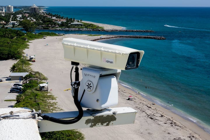 mounted camera on building hanging over beach with ocean and inle