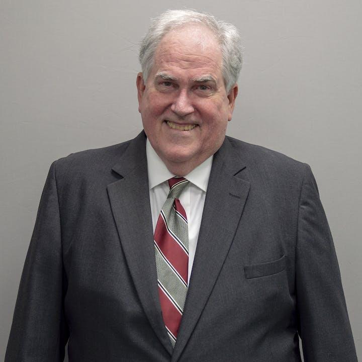 headshot of William Broome in suit and tie