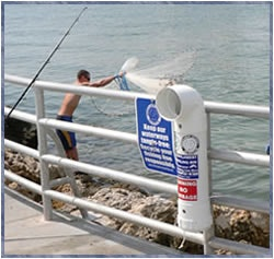 person net fishing off rocks beyond jetty concrete deck with PVC fishing line disposal container in foreground