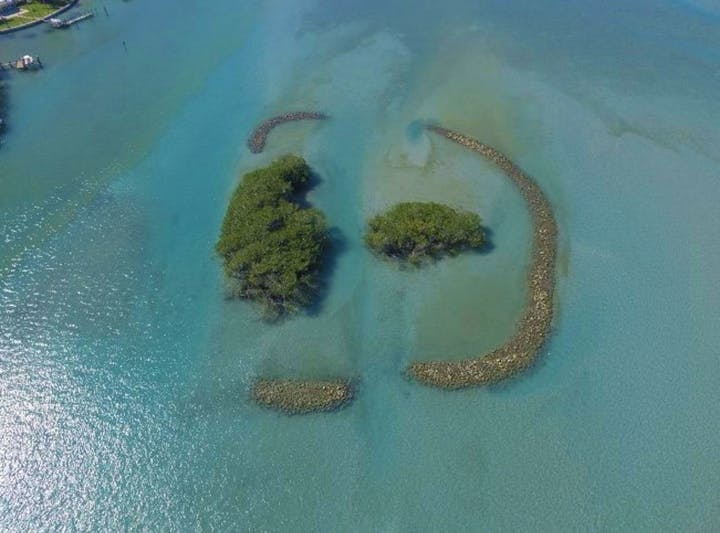 small islands with breakwaters in blue water