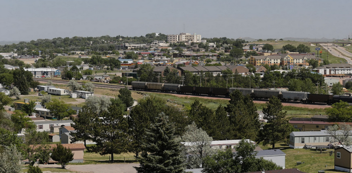 May contain: urban, rail, transportation, train track, railway, neighborhood, building, plant, tree, fir, and abies
